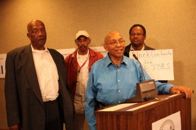 "Dr. Willie Ratcliff, Bay View publisher and owner of Liberty Builders, campaigning for a greater role for Blacks in school construction, testified at a School Board meeting, backed by fellow contractors Charlie Walker and Muhammad al-Kareem and by Mike Brown, whose sign tells a fundamental truth, ""Black contracts for Black jobs!"" – Photo: Ken Johnson"