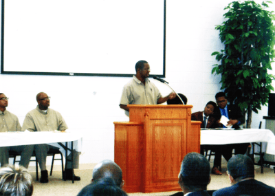 Before a crowd of 250, including White House officials, the USP Atlanta Debate Team, led by Dr. Belay Reddick, shown delivering his team's closing argument, debated the prestigious Morehouse College Debate Team. – Photo: WADE