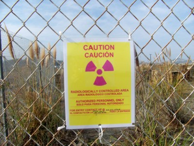 "When this photo was taken in 2007, these ""Caution"" signs were everywhere, warning people that the area is radioactive. Yet construction of new homes that families are already living in went on unabated. – Photo: Bob Nichols"