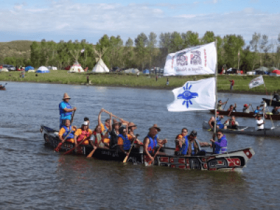 Canoes powered by Nisqually, Puyallup, Quinalt, Chehalis-Colville, Kalispel, Warm Springs, Coeur d'Alene, Kootnai and Tlingit-Haida people arrive from Washington, Idaho, Oregon, Minnesota and Alaska on Sept. 9. Having paddled for two days down the Missouri River from Bismark to Standing Rock, they were welcomed exuberantly at the Sacred Stone Camp. Traveling the longest distance were the Tlingit-Haida people in a dramatic red and black traditionally decorated canoe. – Photo: © Zoltan Grossman