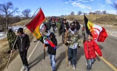 Hundreds of Indigenous people march to commemorate the 1973 Wounded Knee occupation and demand Leonard Peltier's freedom on Feb. 27, 2014.