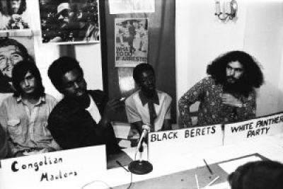 Pun Plamondon of the White Panther Party listens as a member of the Black Berets speaks at a press conference held by Ann Arbor radical groups. – Photo: ©Herald Co.