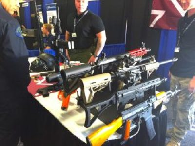 """Cops admire these """"less lethal"""" weapons on display inside the Urban Shield expo that the photographer says """"shoot pepper and glassbreaker rounds,"""" adding that sales are reportedly growing because of """"recent events."""" – Photo: Mary Noble"""