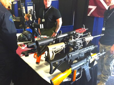 "Cops admire these ""less lethal"" weapons on display inside the Urban Shield expo that the photographer says ""shoot pepper and glassbreaker rounds,"" adding that sales are reportedly growing because of ""recent events."" – Photo: Mary Noble"