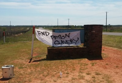 "On April 9, 2016, supporters holding a rally outside Holman Prison to draw attention to Free Alabama Movement's campaign to end prison slavery placed a banner on top of the sign identifying ""W.C. Holman Correctional Facility."""