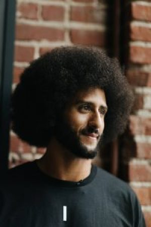 """Pleased with a job well done, Kaepernick smiles at the end of a long day. He muses: """"A lot of these communities have been oppressed for so long and talked down to for so long that it might take one person to spark that thought or that confidence that, 'You know what, my life matters, what I do matters, and I can succeed regardless of the oppressive nature of the system I have been put in.'"""" – Photo: Katrina Britney Davis, The Undefeated"""