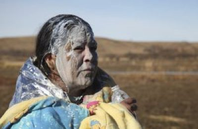 This elder was one of the water protectors who swam across the creek and was recovering after being treated – apparently with Maalox – for a heavy dose of pepper spray. – Photo: John Mone, AP