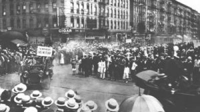 """In this scene from Marcus Garvey's UNIA parade in Harlem in 1924, a sign in the lead car is visible reading """"The New Negro has no fear."""""""