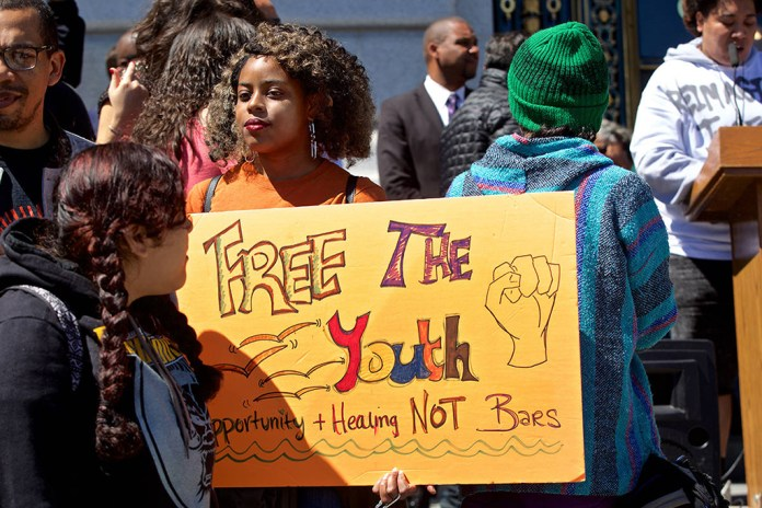 Rally-to-close-SF-Juvenile-Hall-by-2021-young-woman-holds-'Free-the-Youth'-sign-City-Hall-steps-040919-by-Kevin-N.-Hume-SF-Examiner, Youth and SF Board majority back Shamann Walton's proposal to close Juvenile Hall because 'all you learn is how to survive in prison', Local News & Views