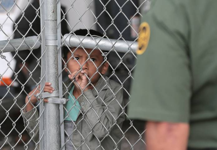 Migrant-child-looks-thru-fence-at-border-officer-by-Tiny, Caging poor people: Occupied Land Truth Tour through Southwest Turtle Island, National News & Views