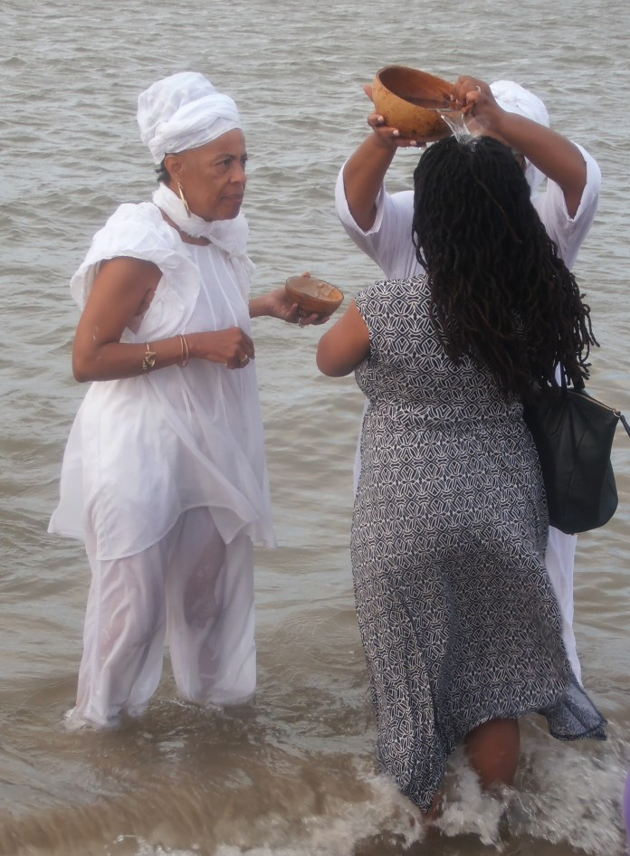 Dr.-Muhjah-Shakir-provides-sacred-oceanic-cleansings-for-participants-on-African-Landing-Day-082419-by-Jahahara, When Our Ancestors Speak … LISTEN!, Culture Currents