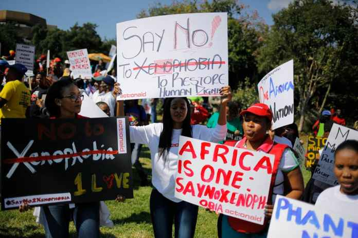 African protesters holding signs that say No to Xenophobia.