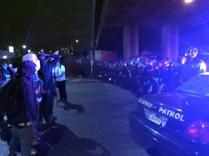 Protesters regroup in front of a police line under Interstate 880 in Oakland. (Alex Emslie/KQED)