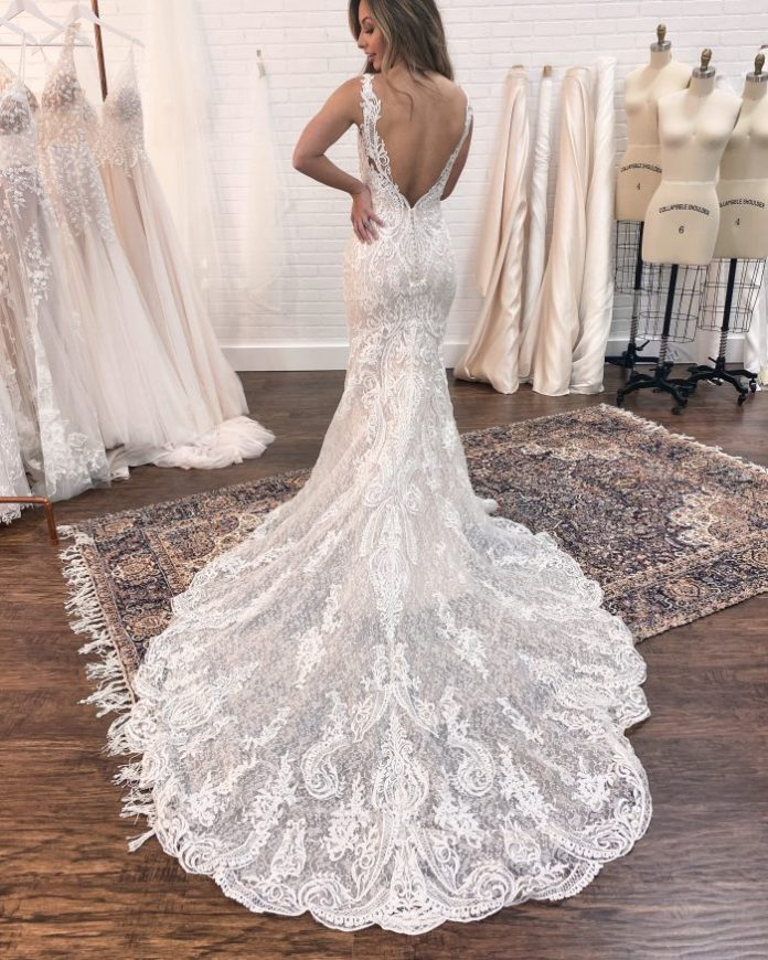 Braut, die den Rücken ihres Maggie Sottero Hochzeitskleiderzuges bei der Hochzeitskleidanpassung zeigt