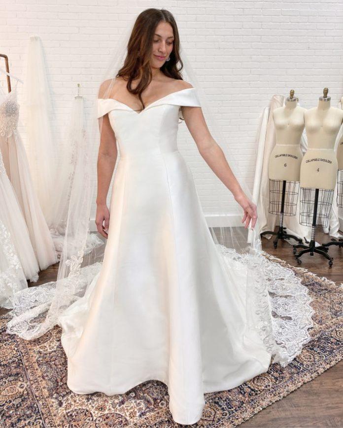 Braut trägt Satin A-Linie Brautkleid genannt Coral von Rebecca Ingram bei Hochzeitskleid Fitting