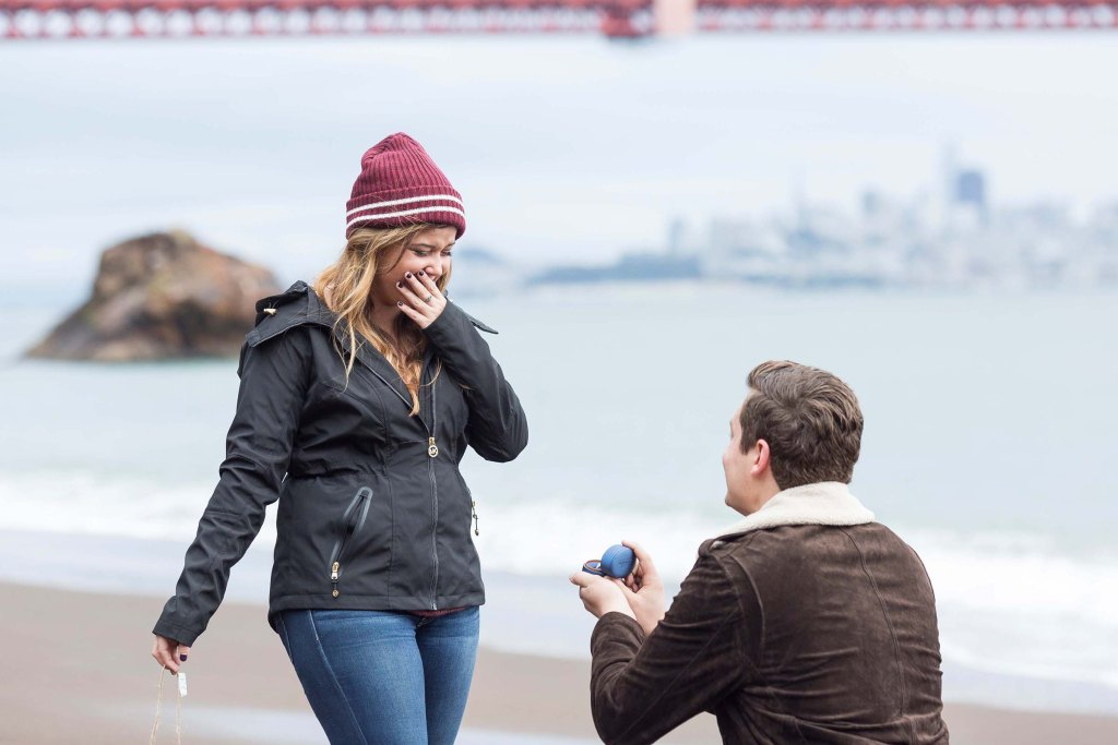 kirby cove marriage proposal with a guy in a brown jacket on his knee holding a ring to his girlfriend who is wearing a black jacket and red beanie