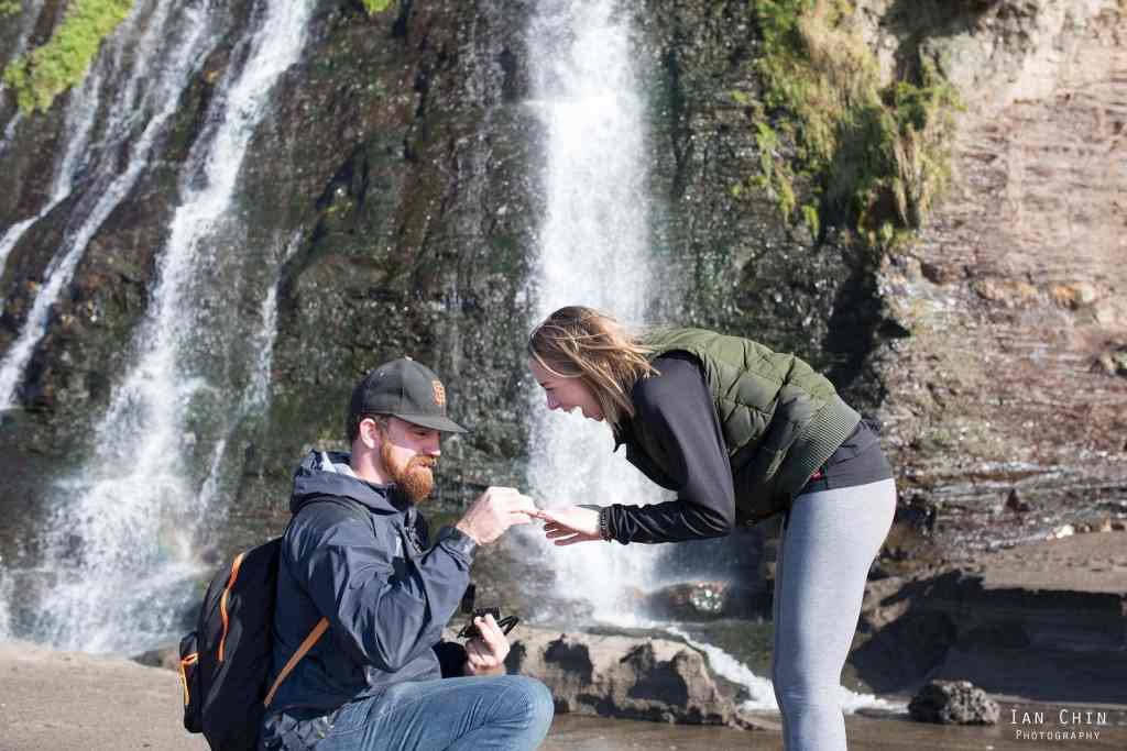 Alamere Falls marriage proposal guy on his knee wearing a baseball cap while the girl is bent over excited