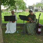 Two women in the shade of a tree playing guitar and violin in traditional dress
