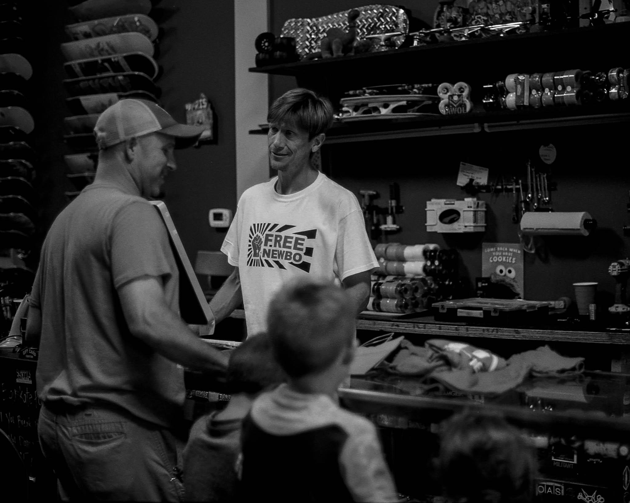 Nate talks to customers at his skateshop, Eduskate