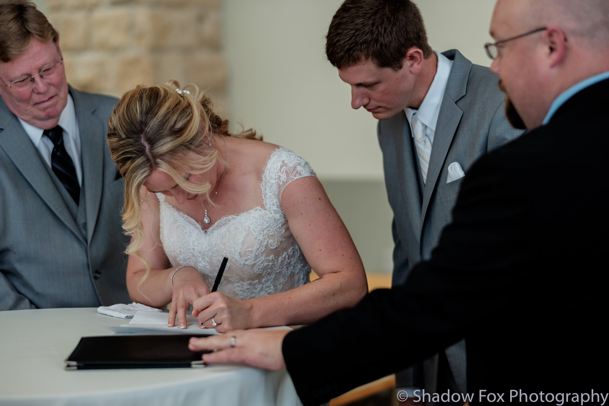 Bride and groom signing wedding certificate after their ceremony