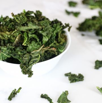 bowl of spicy kale chips with kale chips scattered around