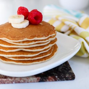 a plate of pancakes with raspberry and banana slices on top