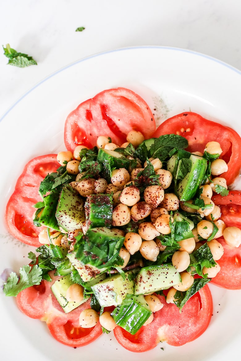 plate of chickpea herb salad on a bed of sliced tomatoes