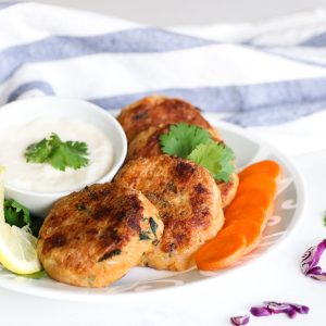 plate of tuna potato cutlets with white dip and carrots and lemon