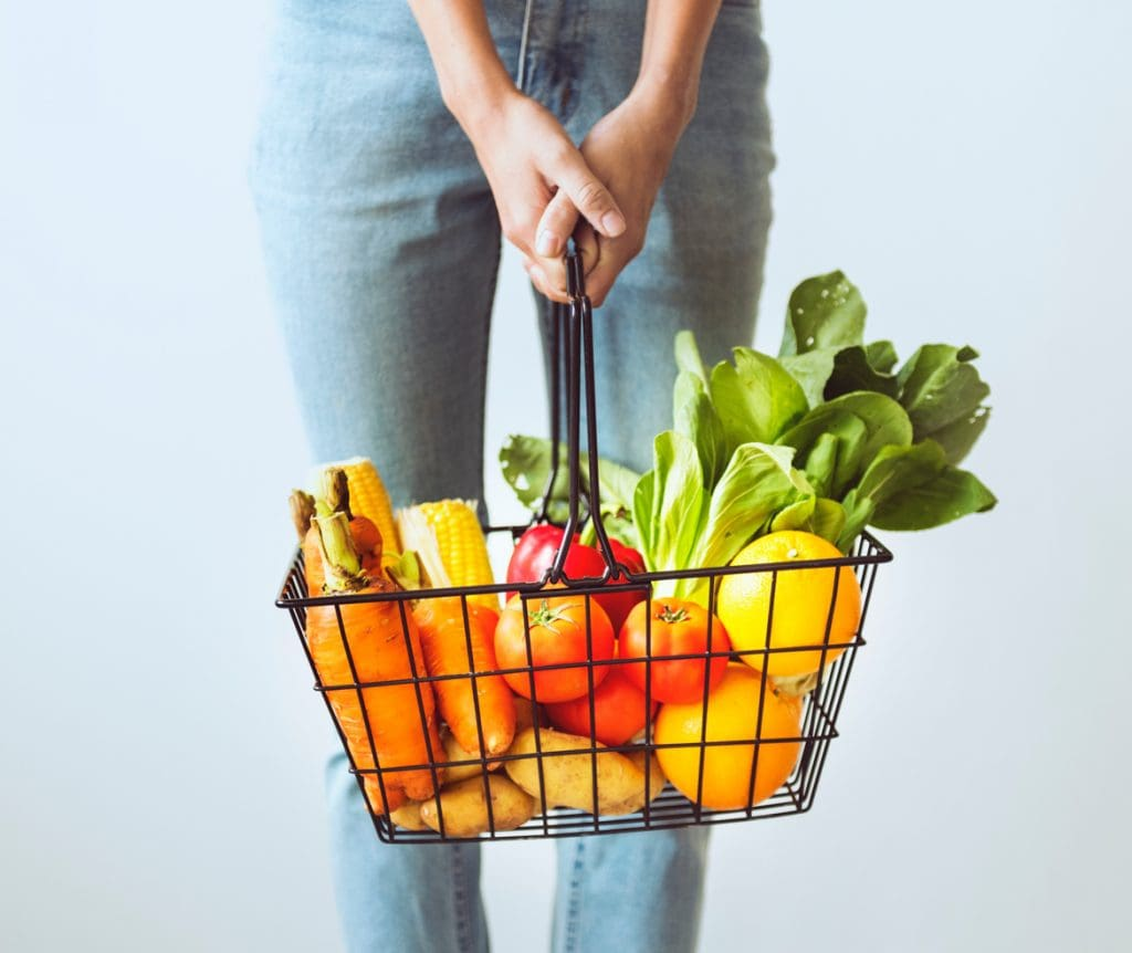 someone holding a basket full of colourful fruits and vegetables