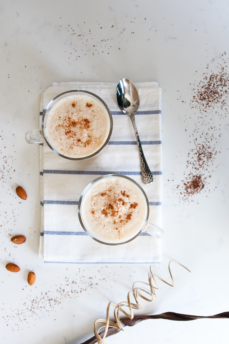 2 cups of chai latte tea with cinnamon sprinkled on top