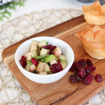 bowl of cranberry and apple salsa with filo cups on a wooden board with dried cranberries