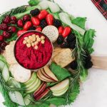 colourful platter of fruits and vegetables with crackers around a bowl of beet hummus