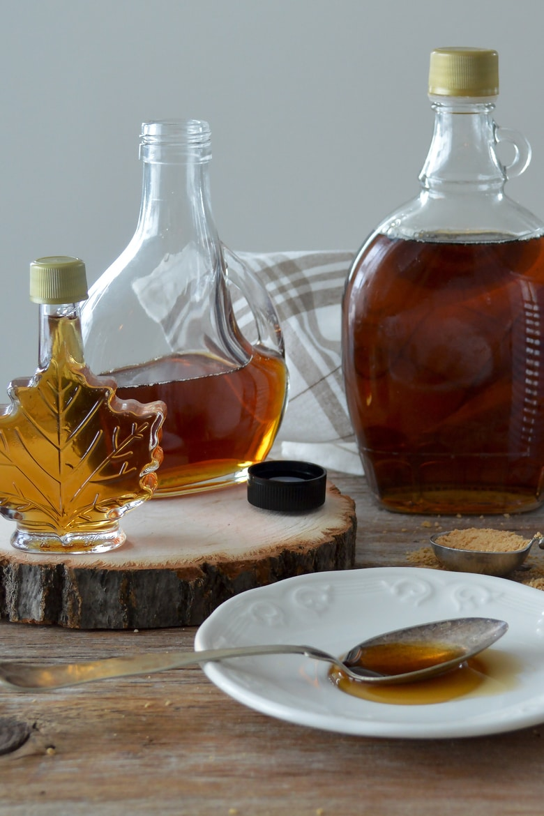 three bottles of maple syrup with a spoon of maple syrup