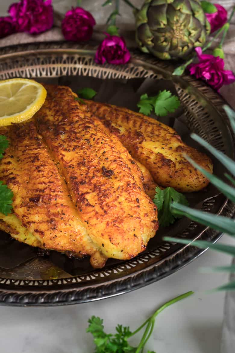 spicy basa fillets on a tary with lemon slices and cilantro on top and flowers around the tray