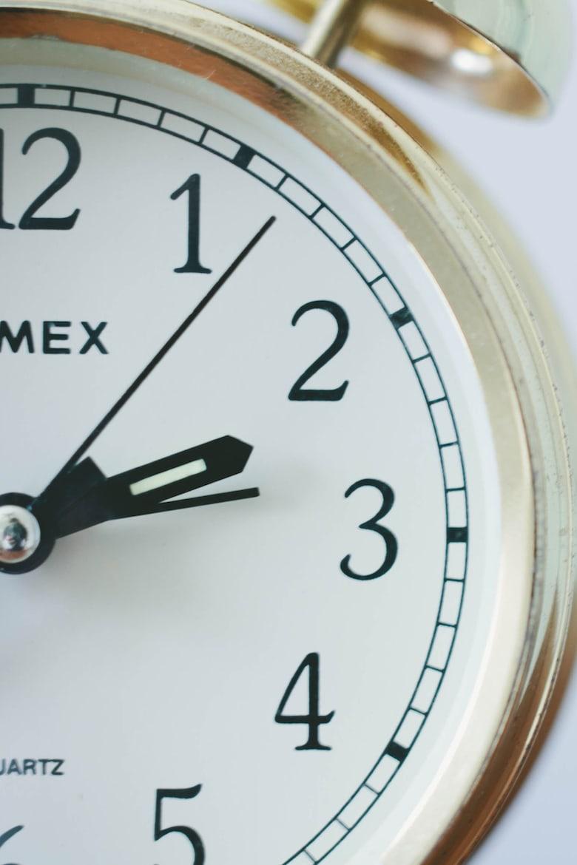 gold alarm clock showing 2 o'clock
