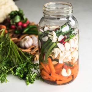 jar of mixed vegetables submerged in water with vegetables on a tray in the background.