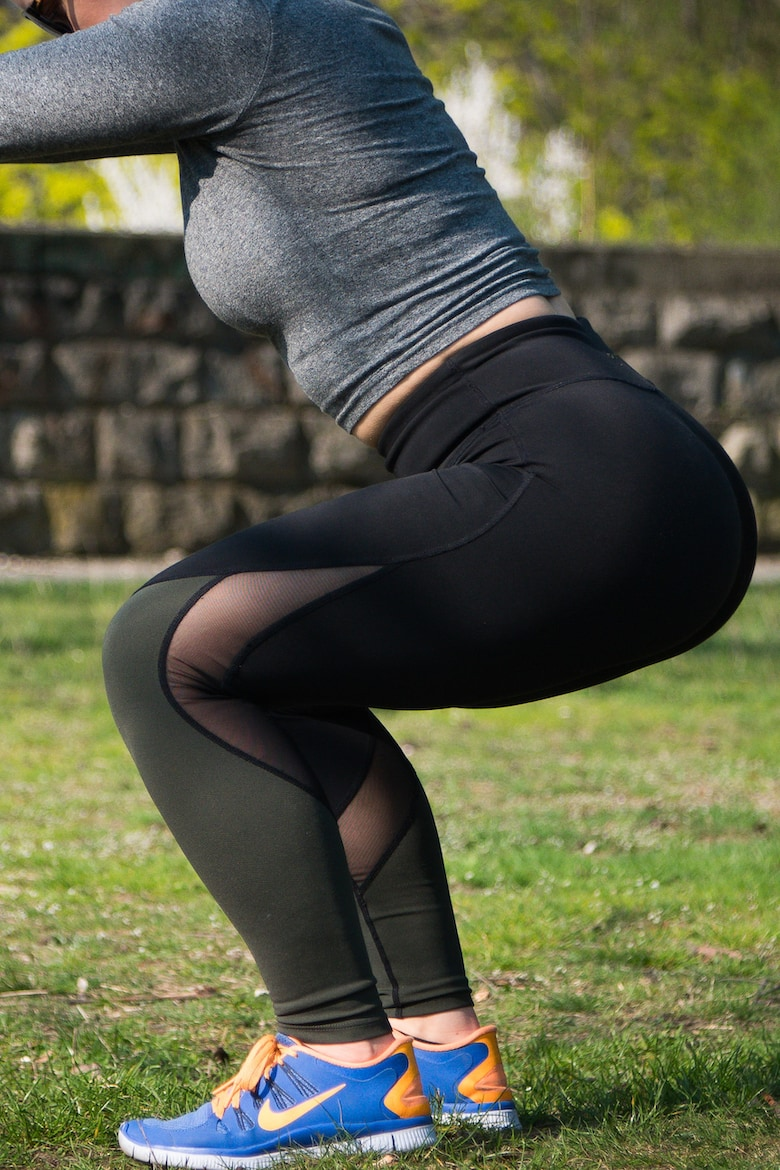Lady doing squat in gym gear