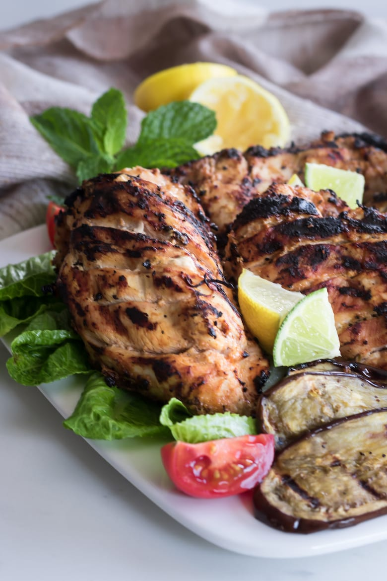 grilled tandoori chicken served with grilled vegetables and lime slices.