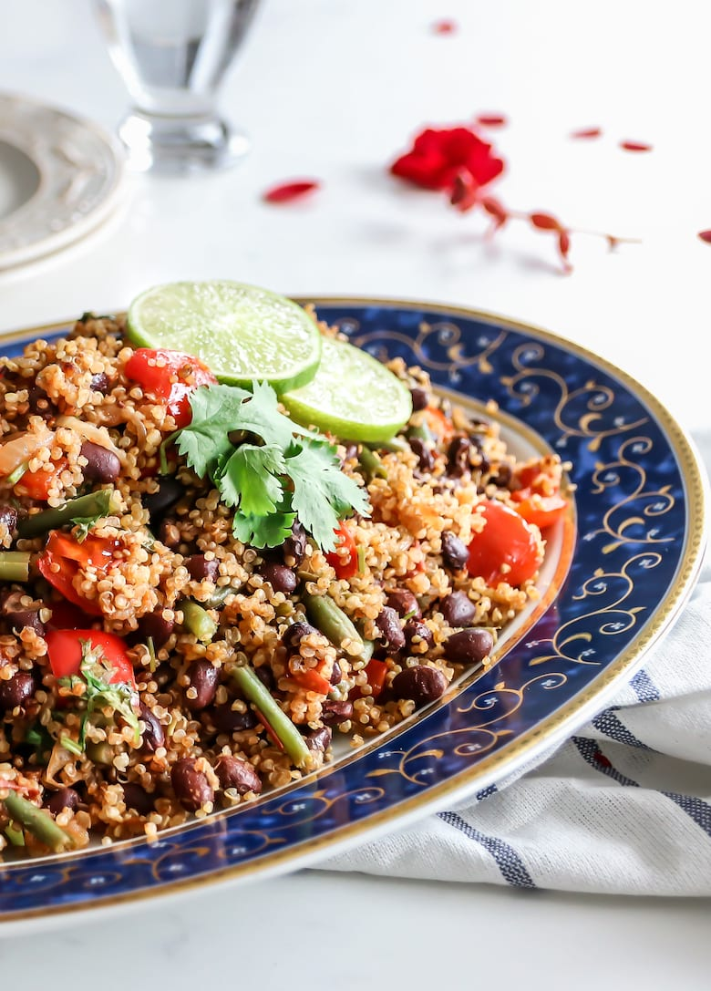 plate of quinoa pilau with tomato, water and empty plates and forks on the side