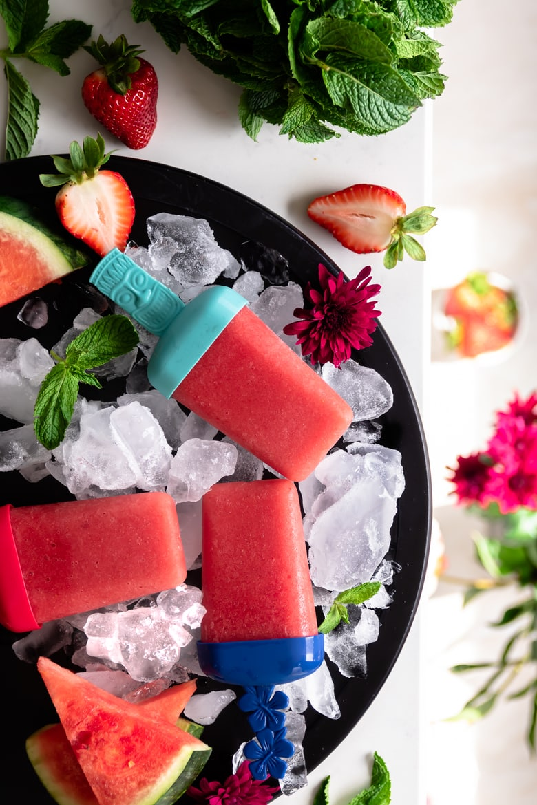 3 strawberry popsicles on ice on a round plate decoratd with fresh watermelon and flowers