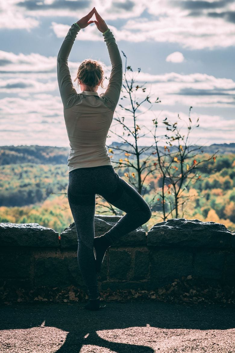 a woman doing the tree yoga pose outdoors, overlooking greenery