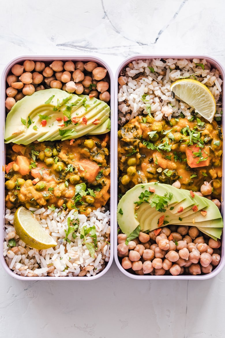 two rectangular lunch boxes with chickpeas, curry, rice and sliced avocados