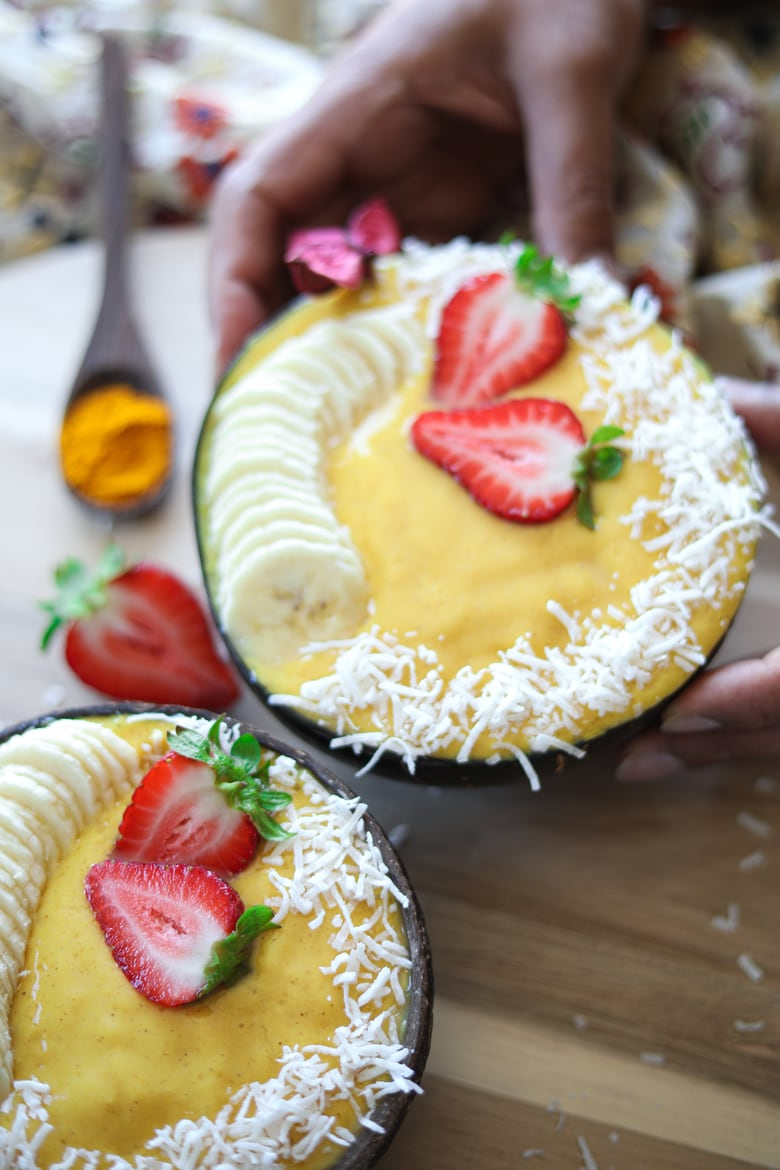 two coconut bowls filled with pineapple mango smoothie decorated with sliced bananas and fresh strawberries