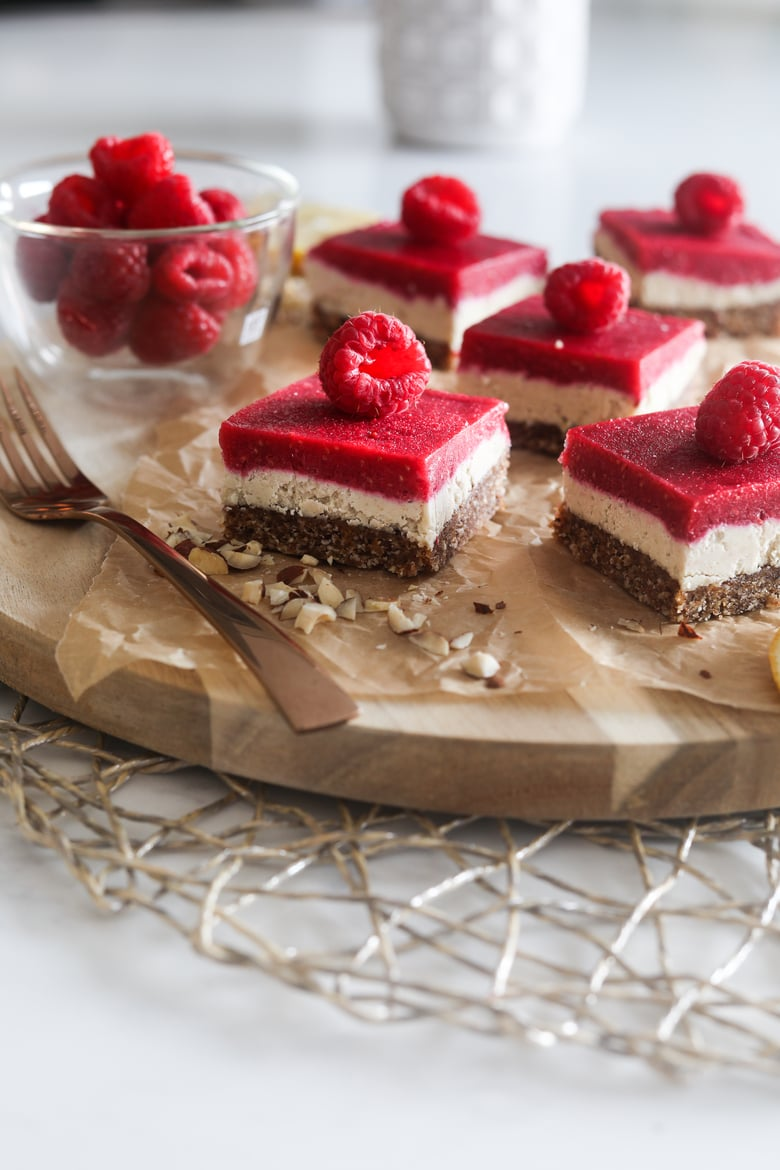 five raspberry vegan bars with a raspberry on each slice, placed on a wooden board with sprinkle of chopped nuts.