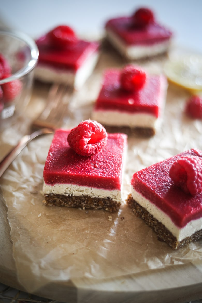 five raspberry vegan bars with a raspberry on each slice, placed on a wooden board