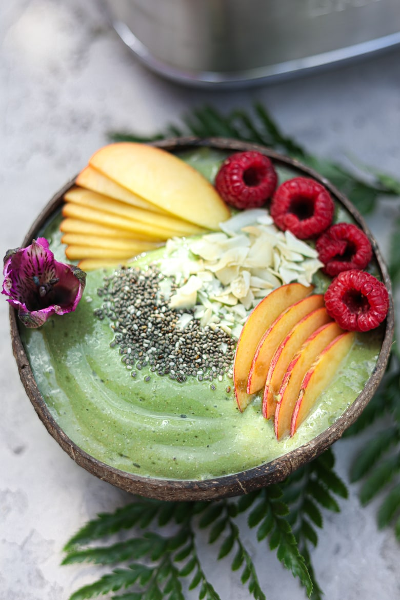 green smoothie bowl topped with sliced peaches, raspberries, coconut and chia seeds