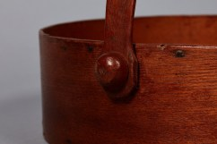 Round carrier of ash and white pine, made at Mount Lebanon's Second Family. Detail views of the pin and locking pegs that fasten the swing handle to the rim. Shaker Museum | Mount Lebanon, 1993.3.7.