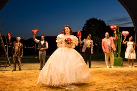 """The Taming of the Shrew's"" Kate wears a wedding dress. Guests, holding red, heart-shaped balloons, assemble behind her."