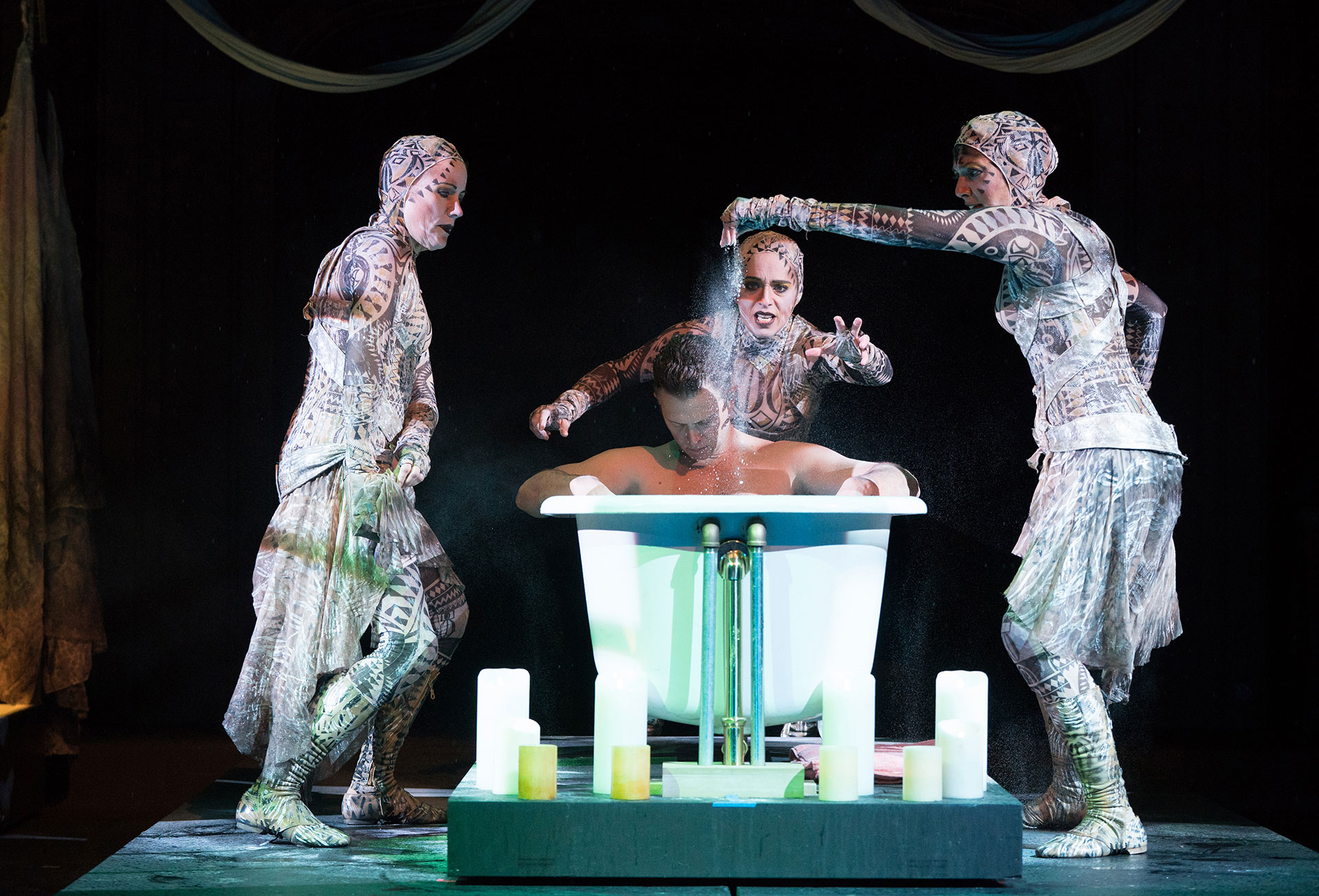 "Three witches surround Macbeth, seated in a bathtub, in ""Macbeth' at Oregon Shakespeare Festival"