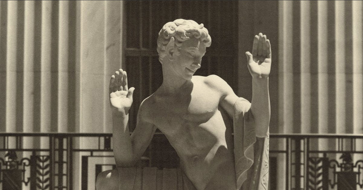 statue of Puck with hands upraised